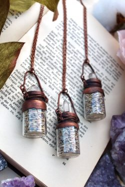 lavender necklace in a bottle with a clear quartz point